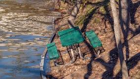 Picknicktisch auf Seite des Hügels nahe dem Rand des Wassers, unbequem lehnend in Richtung zum Wasser lizenzfreie stockbilder