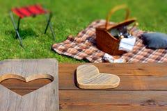 Picknicktisch mit hölzernem Herzen, Decke und Korb im Gras Stockbild