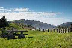 Picknicktisch und Zaun am szenischen Ausblick des Gipfels, Makorori-Landspitze, nahe Ostküste Gisborne, Nordinsel, Neuseeland Stockfotografie