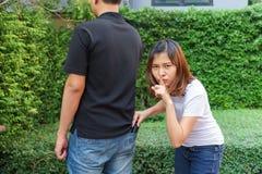 Pickpocket féminin volant un portefeuille par derrière la poche sur des jeans photo stock