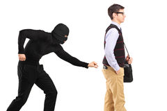 A pickpocket with mask trying to steal a wallet. Isolated on white background stock photo