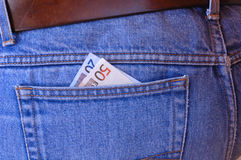 Pickpocket's delight - Euros. Two Euro notes poke out of the rear pocket of a traveller's jeans. Tempting to a pickpocket Stock Photo