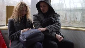 Pickpocket stealing phone from a woman`s handbag in tram or bus.  stock footage