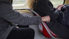 Pickpocket stealing phone from a woman`s pocket in tram or bus.  stock video