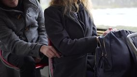Pickpocket stealing phone from a woman`s pocket in tram or bus.  stock video footage