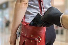 Pickpocket thief is stealing smartphone from red handbag.  stock photos