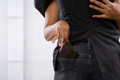 Pickpocket the wallet. Female hand pickpocketing wallet from businessman's pocket, a concept for money thief Stock Photography