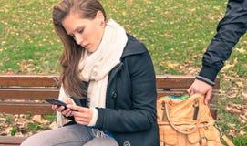 Pickpocketing del bolso de una mujer joven en un parque Fotografía de archivo