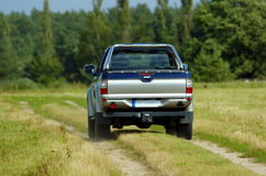 Pickup. Silver pickup on a small way across the field in summer from the back stock photography