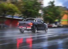 Pickup goes on the rainy city street Royalty Free Stock Photos