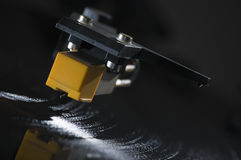 Pickup on grooves of LP. Close-up of a turntable cartridge on a spinning LP in tilted tilt against dark Background; shiny  grooves Stock Image