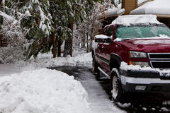 Pickup in a snowy driveway. Red pickup in a freshly leared driveway surrounded by snow Royalty Free Stock Photography