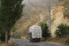 Pickup Truck Carrying Bags. A pickup truck loaded with white bags driving on a rural road in Lebanon stock image