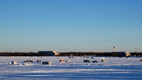 Pickup truck drives past Winter Fishing Houses on frozen Lake Bemidji in Minnesota on a late December afternoon. Pickup truck drives past Winter Fishing Houses stock footage