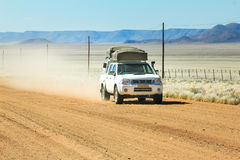 Pickup truck driving fast with dust cloud on desert road Royalty Free Stock Photos