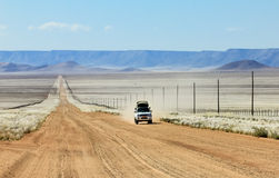 Pickup truck driving fast on long straight desert road royalty free stock photos