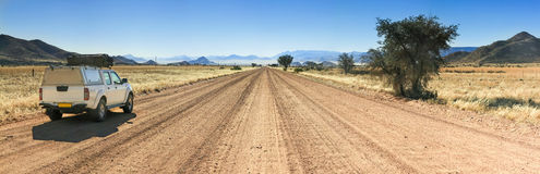 Pickup truck driving on long straight desert road towards mountains. royalty free stock photo