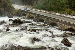 Pickup truck driving on old stone bridge crossing river rapids. Royalty Free Stock Image