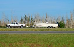 Pickup truck hauling boat. Pickup truck towing fishing boat to marina royalty free stock image