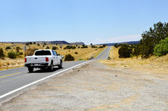 Pickup truck on highway. Rear view of pickup truck on highway in New Mexico desert landscape Royalty Free Stock Image