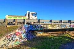 Pickup truck speeds by on a graffiti covered bridge royalty free stock photos