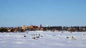 Pickup Trucks Drive on Frozen Lake Bemidji. Pickup trucks drive by Winter Fishing Houses on frozen Lake Bemidji in Minnesota on a late December day with clear stock video footage