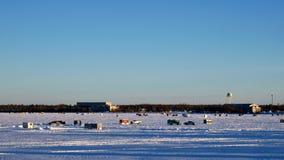 Pickupet kör förgångna vinterfiskehus på den djupfrysta sjön Bemidji i Minnesota på en sen December eftermiddag arkivfilmer