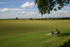 Picnic. A couple taking rest on a green field, by fine weather Stock Image