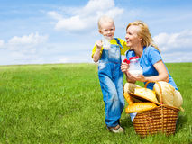 Picnic. Happy young  woman and her son having a picnic outdoor on a summer day Stock Images