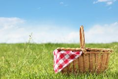 Picnic basket in the grass. Outdoor picnic at sunny day Stock Photo