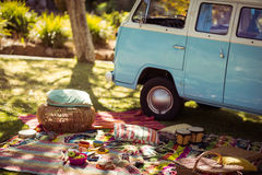 Picnic accessories scattered on blanket next to campervan in park Stock Photo