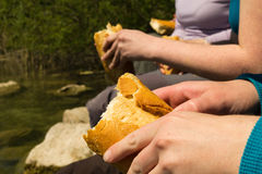 Picnic al fresco. People enjoying a picnic in front of a stream, eating baguette bread Stock Images