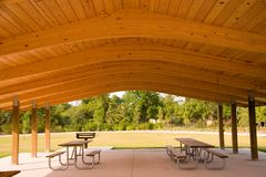 Picnic area. Picnic tables and grill under wood roof structure Royalty Free Stock Photos