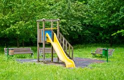 Picnic area and children`s games in the park amid the tall grass. Picnic area, benches and games for children with a yellow slide in the tall grass Royalty Free Stock Images