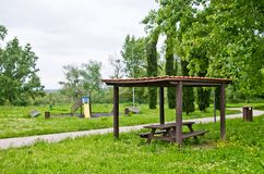 Picnic area and children`s games in the park amid the tall grass. Picnic area, benches and games for children with a yellow slide in the tall grass Royalty Free Stock Photos