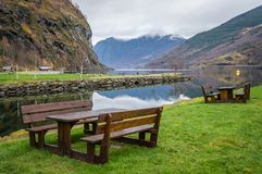 Picnic area on the fjord shore. Wooden benches on a lawn in resting picnic area on the shore of a fjord in small village Flam, Norway Stock Images