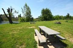 Picnic area in France. A picnic area with wooden tables and wooden bench seats to have a leisurely meal and glass of best French wine on a lovely sunny day in Royalty Free Stock Photo