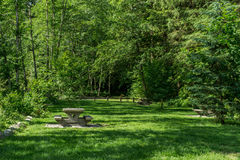 Picnic area in park with table and field Royalty Free Stock Images