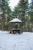 Picnic area with table in the woods in the snow Royalty Free Stock Photos