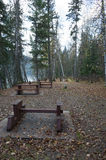 Picnic area with tables alongside a lake. Deserted picnic area with tables alongside a lake with dead autumn leaves on the ground and tall green conifers in the royalty free stock photos