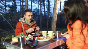 Picnic in the autumn forest in the evening. A loving couple holding hands. A couple in love in the forest at the picnic, they feed each other and hold hands stock footage
