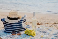 Picnic background with bag, grape and white wine by blue sea. Picnic background with bag, grape and white wine on the beach by blue sea Stock Images