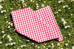 Picnic background. Folded red checkered picnic cloth on a daisy meadow. Topview.  royalty free stock image