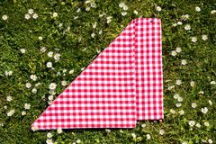 Picnic background. Red checkered picnic cloth on a daisy meadow. Topview.  royalty free stock photography