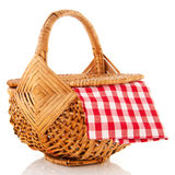 Picnic basket. Wicker picnic basket with checkered red and white table cloth Royalty Free Stock Images