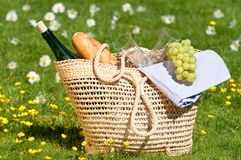Picnic Basket. Packed with wine, glasses, grapes etc. in flower meadow Stock Photo