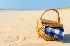 Picnic basket at the beach. Picnic basket with blue checked cloth at the beach Stock Photo