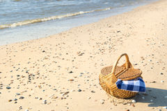 Picnic basket at the beach. Picnic basket with blue checked cloth at the beach Stock Photos