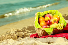Picnic basket on blanket near sea. Relaxation during summertime concept. Picnic basket with fruit on red blanket near sea Stock Image