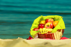 Picnic basket on blanket near sea. Relaxation during summertime concept. Picnic basket with fruit on red blanket near sea Stock Photo